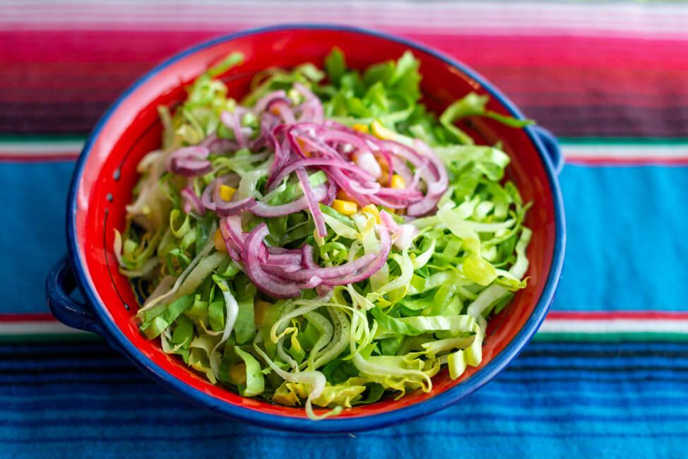 Endiviensalat miz Zwiebeln, Mais und Limetten in bunter Keramikschale auf mexinakischer Tischdecke.