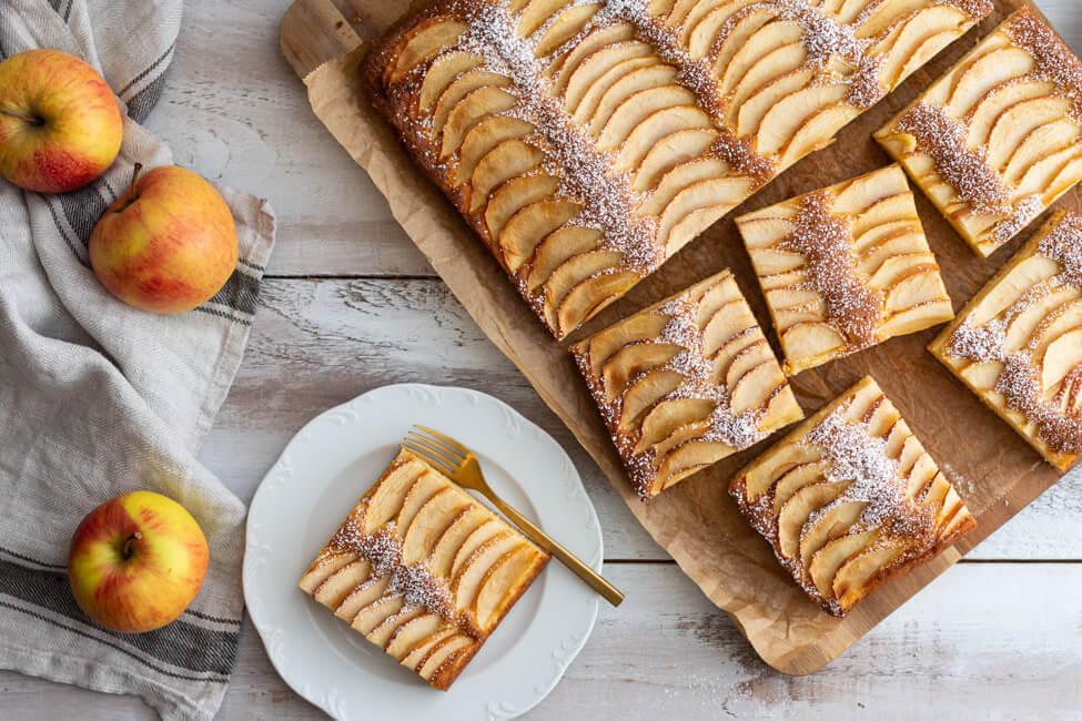Apfelkuchen vom Blech auf einem Schneidebrett und mit Puderzucker bestäubt.
