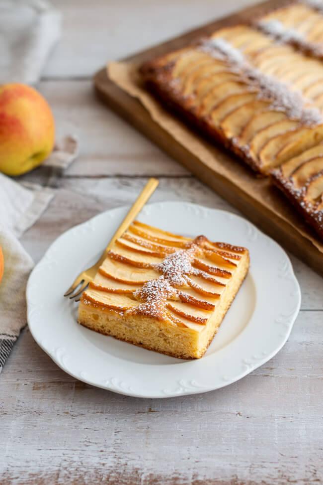 Apfelkuchen vom Blech auf einem Schneidebrett und ein Stück auf einem Porzellanteller,und mit Puderzucker bestäubt.