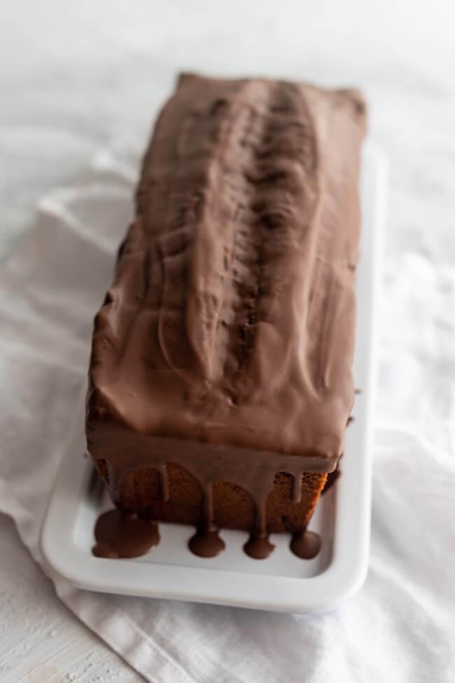 Einfacher Schokoladenkuchen mit Schokoladenglasur auf weißer Kuchenplatte.