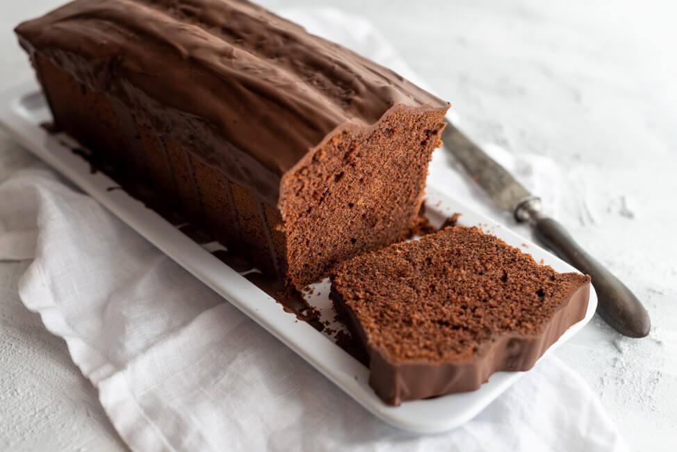 Einfacher Schokoladenkuchen, angeschnitten, mit Schokoladenglasur auf weißer Kuchenplatte.
