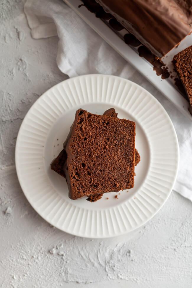 Zwei Stücke vom einfachen Schokoladenkuchen mit Schokoladenglasur auf weißer Kuchenplatte.