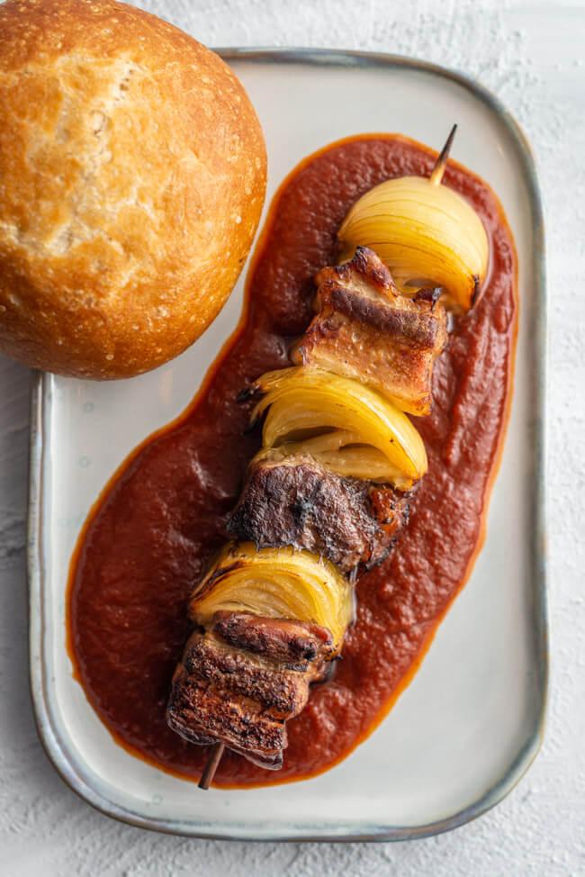 Das weltbeste Schaschlik: Schaschlikspieß mit Fleisch und Zwiebeln auf selbst gekochter Schaschliksoße. Dazu ein Brötchen.