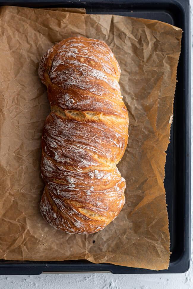 Wurzelbrot frisch aus dem Ofen auf einem Backblech mit Backpapier.