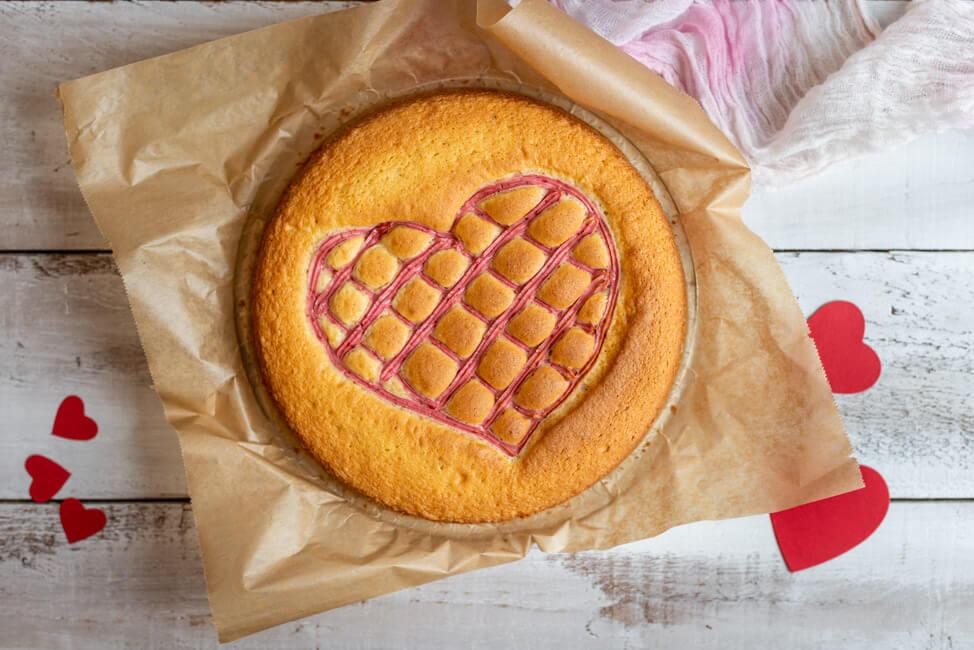 Steppdeckenkuchen für den 14.02.: Herzkuchen zum Valentinstag mit Erdbeerquark auf weißem Holzbrett.