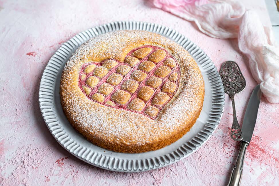 Steppdeckenkuchen für den 14.02.: Herzkuchen zum Valentinstag mit Erdbeerquark auf rosa Untergrund..