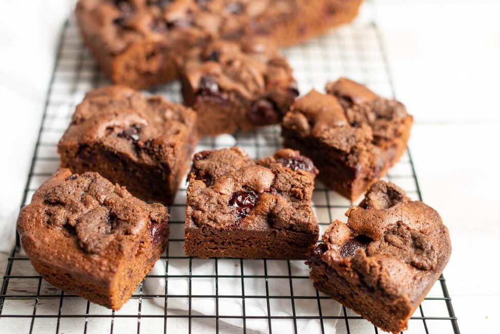 Schokoladen-Blechkuchen mit Rumkirschen und Streuseln auf schwarzem Kuchengitter.