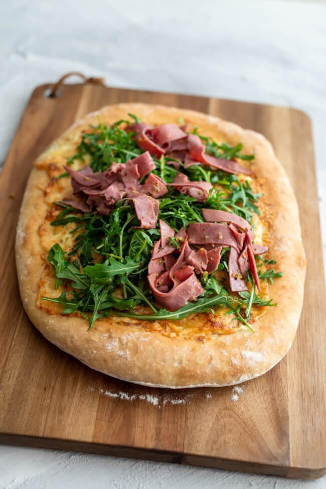 American Pizza bianco mit Rinderbraten Pastrami von Steinhaus und mariniertem Rucola mit Zitrone und Olivenöl..