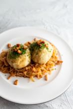 Kitchen Impossible in Salzburg: zwei Grammelknödel auf Veltlinerkraut auf weißem Porzellanteller.
