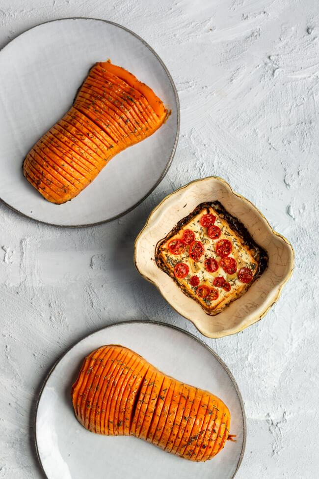 Hasselback Butternuss Kürbis mit mariniertem Feta, mit Tomaten, Knoblauch und Olivenöl, aus dem Ofen.