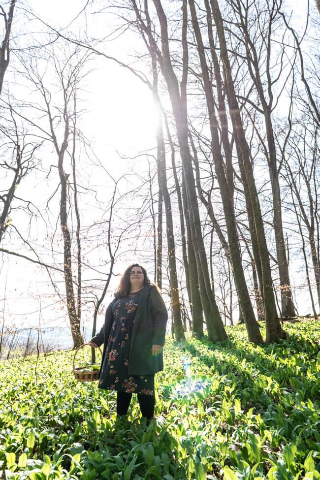 Tina von foodundco.de im Wald beim Bärlauch sammeln im Gegenlicht.
