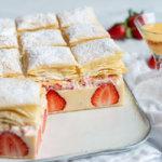 Eierlikör Cremeschnitte mit Erdbeeren, selbst gemachtem Blätterteig und Erdbeersahne auf weißer Keramikplatte.