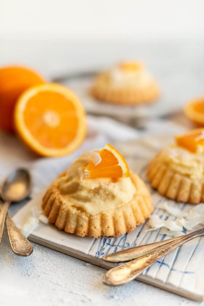 Eistörtchen mit Orangeneis und Kokosrapseln auf Keramikbrettchen.