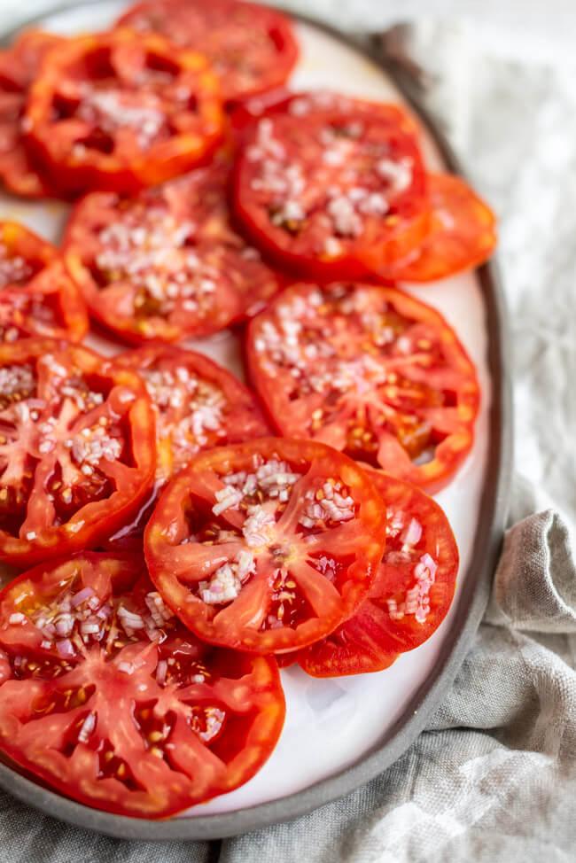 Einfacher Tomatensalat, aus Ochsenherztomaten mit Zwiebel-Vinaigrette, auf weißem Keramikteller.