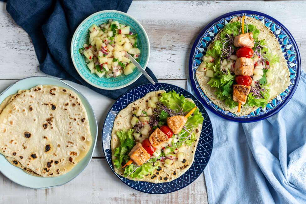 Lachs Tacos mit Melonen-Salsa auf blauen Keramiktellern und weißem Holztisch.