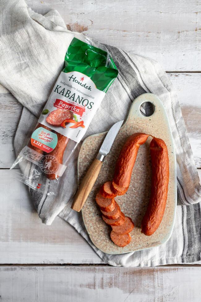Houdek Kabanos Paprika aufgeschnitten auf Keramikbrettchen und Holzmesser.