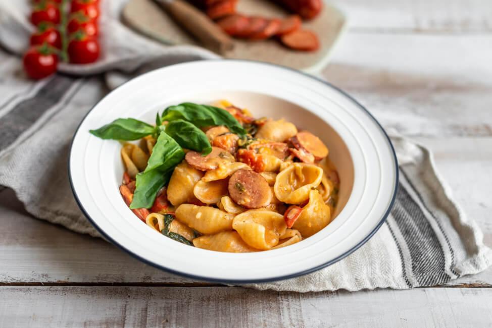 One-Pot-Pasta mit Tomaten, Feta und Kabanos Paprika auf weißem Teller.