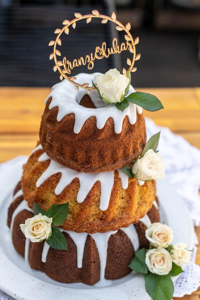 Gugelhupf Hochzeitstorte mit weißen Rosen und Caketopper auf weißem Keramikteller.