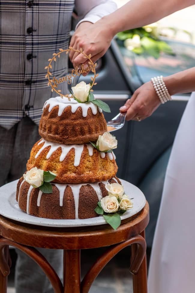 Das Brautpaar schneidet die Gugelhupf Hochzeitstorte mit weißen Rosen und Caketopper an.