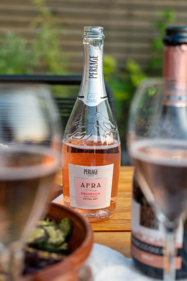 Prosecco DOC Rosé Flasche zwischen Sektgläsern auf gedecktem Tisch.