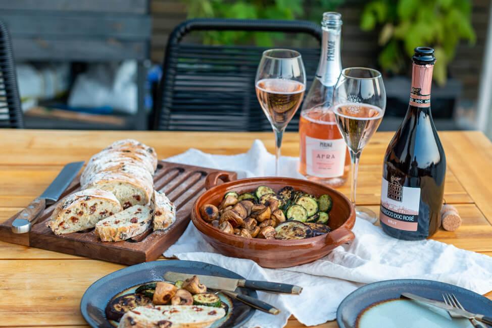 Mediterranes Wurzelbrot mit Antipasti und Prosecco DOC Rosé auf gedecktem Tisch.