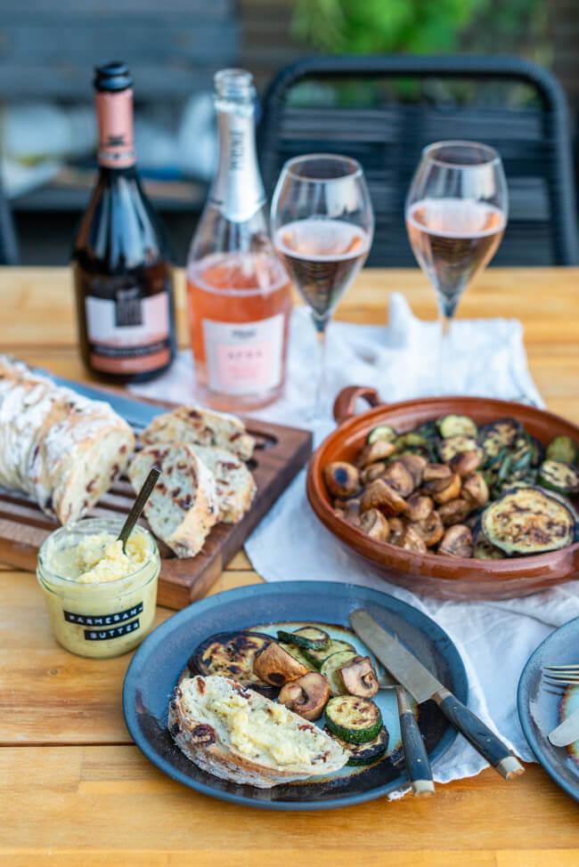 Mediterranes Wurzelbrot mit Parmesanbutter und Antipasti auf rustikalem Teller.