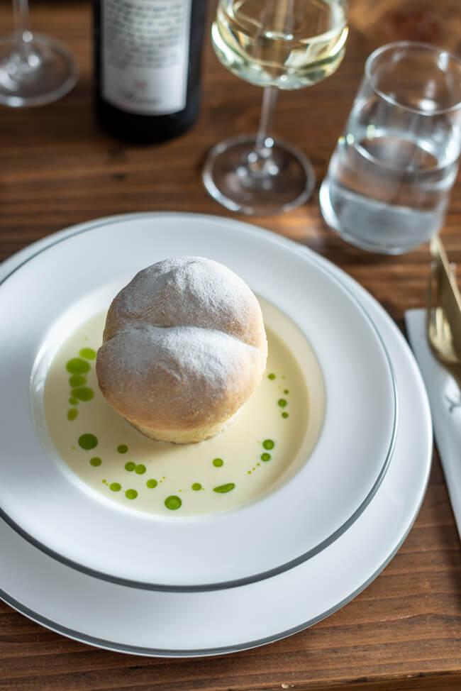Gefüllte Buchteln mit karamellisierten Zwiebeln mit Bergkäse-Sauce und Schnittlauchöl auf weißem Keramikteller.